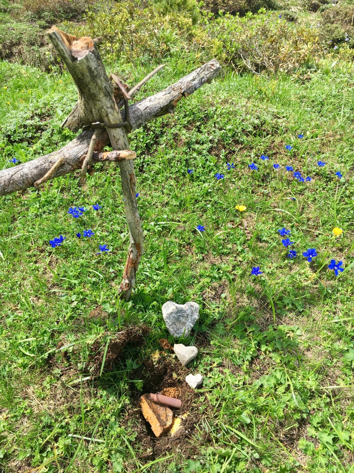 Heilmedizinwanderung - auf dem Weg gefundene Granatsplitter und Gewehrhülsen werden, stellvertretend für die Wunden, begraben